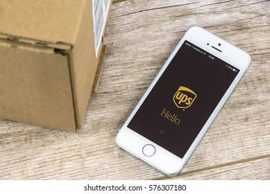 Krynica, Poland - February 10, 2017: UPS tracking shipment app on iPhone SE, close to a parcel post. UPS is one of the largest postal shipping company on the world.