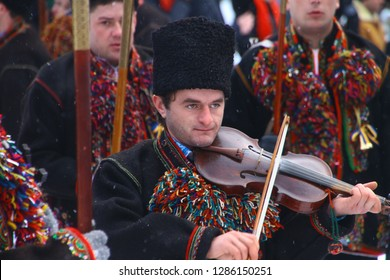 Kryvorivnia, Ukraine - January 7, 2019: Violin player in national Hutsul costume plays traditional old carol song while other men sing during Christmas celebration in Ukrainian Carpathian Mountains.