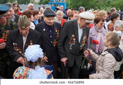 Kryvyi Rih, Ukraine - May 7, 2016: Children give flowers to veterans during event devoted to 71th anniversary of Victory over Nazi Germany in WWII Time of Remembrance and Reconciliation (Victory Day)