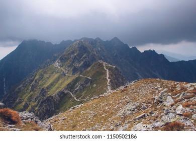 The Krzyzne Pass (Przełęcz Krzyżne) in the High Tatras, Zakopane, Poland. Panoramic view on mountains and dark clouds above them. Mountain chain behid. Amazing landscape shot from Tatra National Park.
