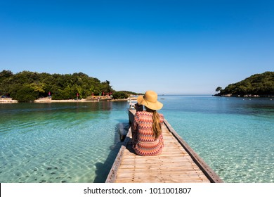 Ksamil Beach - Woman with straw hat sitting on a wooden walkway, Ksamil, Albania