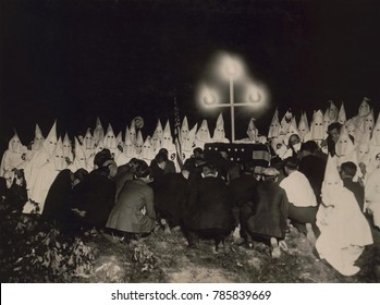 Ku Klux Klan gathered within two miles of the U.S. Capitol to receive new members, c. 1925-27. In the background are shrouded members, with the initiates kneeling in the foreground