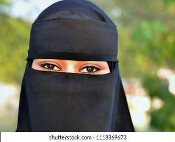 KUAH, LANGKAWI / MALAYSIA - JAN 30, 2016: Young, newly married Sudanese woman on honeymoon in Langkawi, clad in black niqab and burqa, poses for the camera, on Jan 30, 2016.