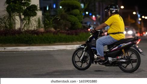 KUALA KANGSAR, PERAK, MALAYSIA - FEBRUARY 22ND, 2020. Motorcycle riders riding motorbikes in a rural Malaysian town. Selective focus.