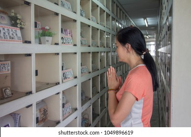 Kuala Lumpur 02 Mac 2018 - an Asian woman standing at Chinese style columbarium paying respect in front of cinerary urns of ancestor during Qing Ming festival. Descendants cleaning tomb at cemetery