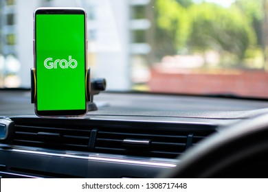 KUALA LUMPUR: 10 FEB 2019 -  Car driver using smartphone with with Grab app on screen.
