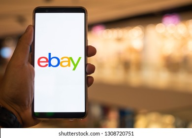 KUALA LUMPUR: 10 FEB 2019 - Hand holding smartphone displaying Ebay app with shopping mall background.