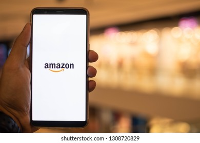 KUALA LUMPUR: 10 FEB 2019 - Hand holding smartphone displaying Amazon app with shopping mall background.