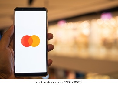 KUALA LUMPUR: 10 FEB 2019 - Hand holding smartphone displaying MasterCard app with shopping mall background.