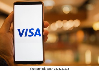 KUALA LUMPUR: 10 FEB 2019 - Hand holding smartphone displaying Visa app with shopping mall background.
