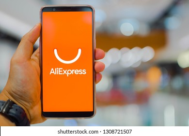 KUALA LUMPUR: 10 FEB 2019 - Hand holding smartphone displaying AliExpress app with shopping mall background.