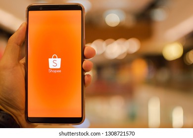 KUALA LUMPUR: 10 FEB 2019 - Hand holding smartphone displaying Shopee app with shopping mall background.