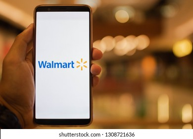 KUALA LUMPUR: 10 FEB 2019 - Hand holding smartphone displaying Walmart app with shopping mall background.
