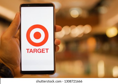 KUALA LUMPUR: 10 FEB 2019 - Hand holding smartphone displaying Target app with shopping mall background.