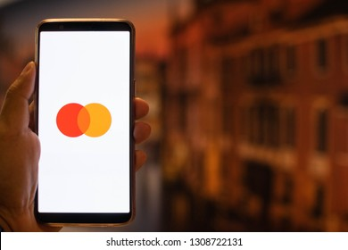 KUALA LUMPUR: 10 FEB 2019 - Hand holding smartphone displaying Mastercard app with European building background.
