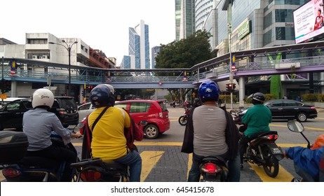 KUALA LUMPUR, 22 MAY 2017: Unidentified motorcyclists and vehicles stand traffic light in the city center. As other Asian countries motorcycle is the most popular and available transport vehicle.