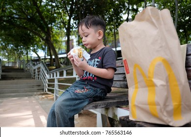 Kuala Lumpur 25 November 2017 : Close up portrait of Asian kid eating McDonald's burger in the park. McDonald's is a fast food restaurant chain founded in 1940.
