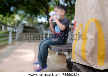 Kuala Lumpur 25 November 2017 : Close up of McDonald's take away paper bag with kid eating burger in the background. McDonald's is a fast food restaurant chain founded in 1940.