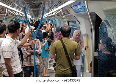 KUALA LUMPUR - AUG 6, 2017: Commuters in a crowded MRT train in Cheras, KL. The MRT is a component of the Klang Valley Public Transport System.