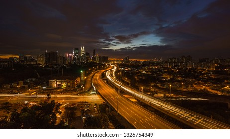 Kuala Lumpur city skyline during dramatic sunset with elevated highway leading into the city.