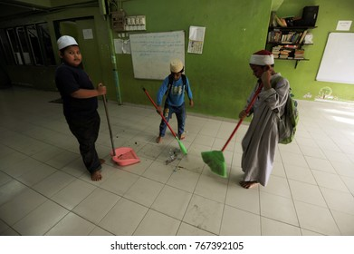KUALA LUMPUR - December 16th 2016: Rohingya children refugees cleaning up their classroom after class session. Thousands of Rohingya refugee fled to Malaysia dued to ethnic criss in Myanmar.