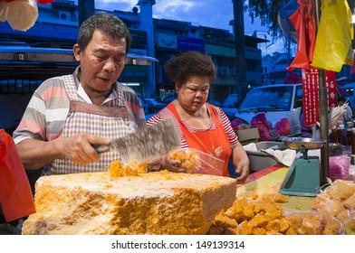 KUALA LUMPUR - JAN 01: Unidentified Chinese couples sell honey rock at traditional night market in Kuala Lumpur, Malaysia on August 7, 2013.