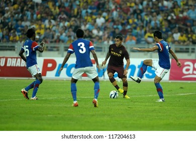 KUALA LUMPUR - JULY 30: Carlos Teves run the ball through Aidil Zafuan(7) and S.Subramaniam (3) during Manchester City friendly match against Malaysia at Kuala Lumpur in July 30, 2012.