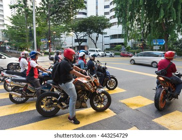 KUALA LUMPUR - JUNE 15, 2016: Unidentified motorcyclists and vehicles stand traffic light in the city center. As other Asian countries motorcycle is the most popular and available transport vehicle.
