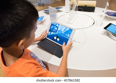 KUALA LUMPUR - JUNE 15, 2016: A boy plays a computer race on an iPad with a keyboard in Suria KLCC mall. iPad is an iOS based line of tablet computers designed and marketed by Apple Inc.