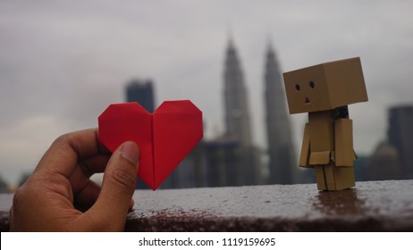 Kuala Lumpur - JUNE 2018: Cute Danbo character lovingly holds out a red heart background town city KL.