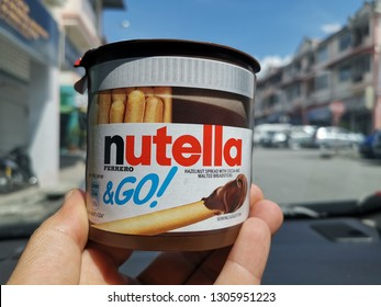 Kuala Lumpur, Malaysia - 03 February 2019: Hand holding a Nutella & Go chocolate cream with brot-sticks. Nutella is Italian world's famous chocolate cream by Ferrero industry