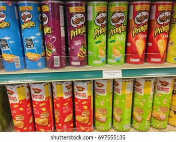 Kuala Lumpur, Malaysia - 10 August 2017: Rows of various flavored chips from different brands on display rack of a supermarket. Several varieties of Pringles and Mister Potato brand potato chips.