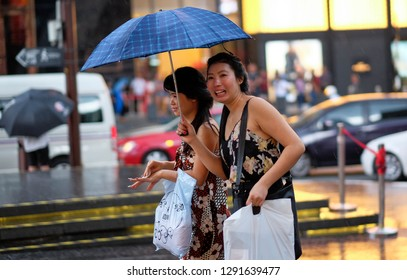 Kuala Lumpur, Malaysia 10 Jan 2019: Street scene of people with umbrella during rainy day in Bukit Bintang shopping area.