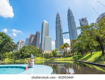 KUALA LUMPUR, MALAYSIA - 12 JULY 2016: The Petronas Twin Towers photo taken during sunny afternoon from KLCC park with some tourist.