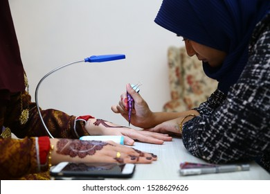 Kuala Lumpur, Malaysia 12 October 2019 - Artist applying henna tattoo on women hands. Brides wearing Perak states in Malaysia traditional dress