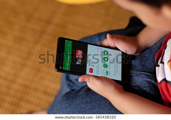 Kuala Lumpur, Malaysia - 14 Feb : Kid watching youtube on smartphone. Smartphone safety for kids is now a big concern for parents.