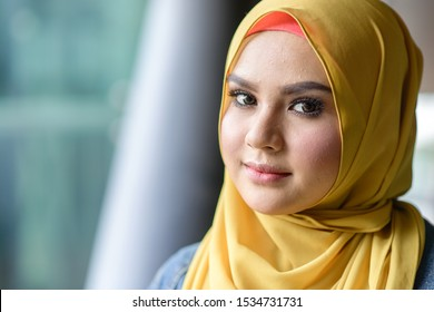 Kuala Lumpur, Malaysia -  15 Oct, 2019 : Portrait of a beautiful Malay woman wearing a hijab outdoors backlit by sun, shot with flares.  Muslim female hijab fashion portraiture concept.