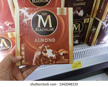 Kuala Lumpur, Malaysia - 18 March 2019: Hand of a man holding box Magnum Almond Chocolate ice cream in supermarket