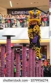 KUALA LUMPUR, MALAYSIA - 19 OCT 2014 : Yellow color lion dance performing its stunts on high poles at VIVA HOME shopping mall in Kuala Lumpur, Malaysia.