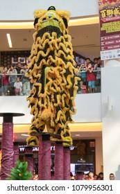 KUALA LUMPUR, MALAYSIA - 19 OCT 2014 : Lion dance performance on high pole at VIVA HOME shopping mall in Kuala Lumpur, Malaysia.
