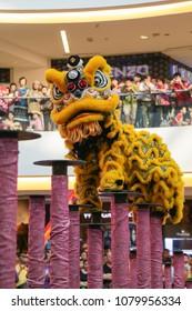 KUALA LUMPUR, MALAYSIA - 19 OCT 2014 : Yellow color lion dance performing his stunts on high poles at VIVA HOME shopping mall in Kuala Lumpur, Malaysia.