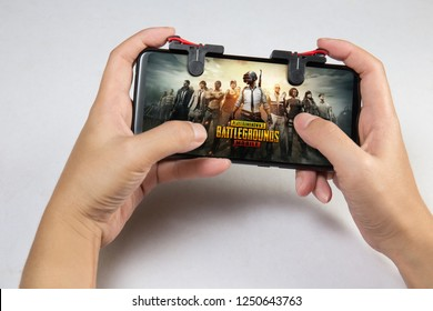Kuala Lumpur, Malaysia - 2 December 2018: Hand holding a smartphone with Player's Unknown Battleground also known as PUBG online shooting gaming