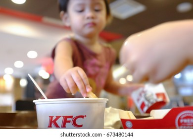 Kuala Lumpur, Malaysia 2 July 2017 : Asian kid enjoy eating Kentucky Fried Chicken (KFC) foods.  KFC, is an American fast food restaurant chain that specializes in fried chicken.