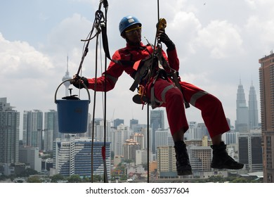 Kuala Lumpur, Malaysia 20 March 2017 : A group of maintenance workers cleaning windows on high rise building in Kuala Lumpur.