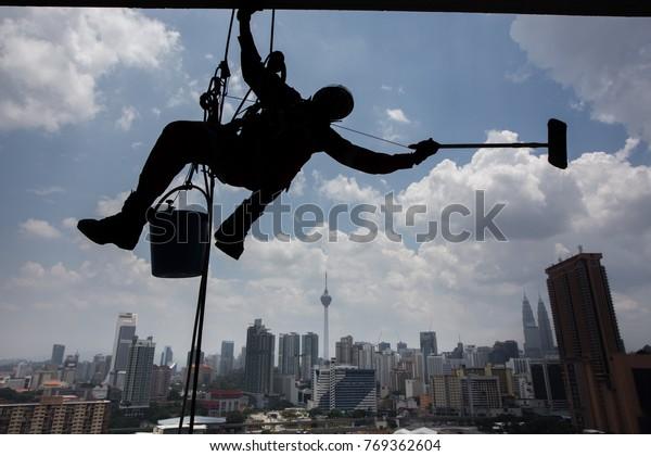 Kuala Lumpur, Malaysia 20 March 2017 : A maintenance workers cleaning windows on high rise building in Kuala Lumpur.