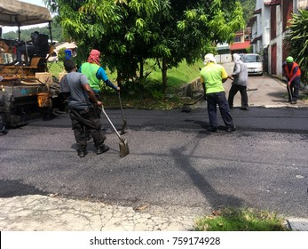 KUALA LUMPUR, MALAYSIA - 21 NOVEMBER 2017 : Laborers working on road paving works in a residential area