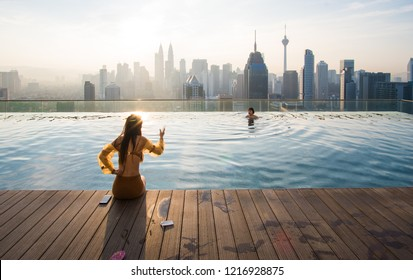 kuala lumpur malaysia 21 october 2018 :a panoramic view of Kuala Lumpur in the morning and at the swimming pool  hotel where some people are swimming and relaxing. with over exposure the sun concept.