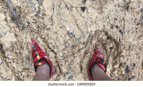 Kuala Lumpur, MALAYSIA - 23 January 2018: Human legs on hiking shoes in road dirt.