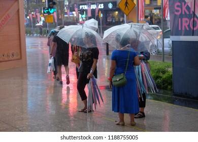 Kuala Lumpur, Malaysia - 25 September 2018 : Street scene of pedestrians using umbrella in Bukit Bintang commercial area of Kuala Lumpur.