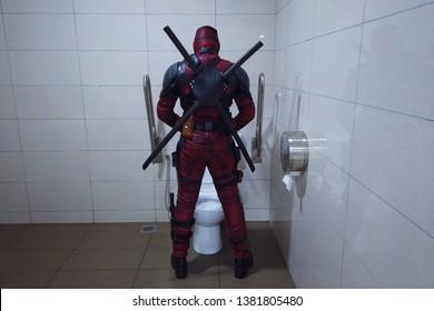 KUALA LUMPUR, MALAYSIA 26 April : Unidentified Deadpool cosplayer peeing to toilet bowl.